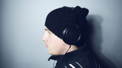 young man with winter hat and headset listening music