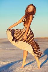 young woman in a long dress dancing in a desert