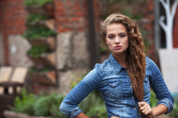Beautiful young girl with curly hair outdoors in denim shirt