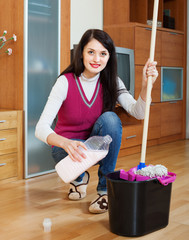 Smiling  woman washing  floor with mop and detergent