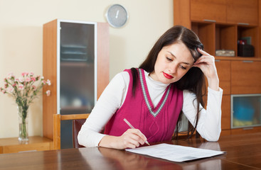 serious brunette woman reading document