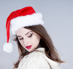 Christmas woman. Beautiful charming girl wearing santa hat over