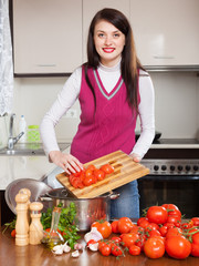 Smiling young housewife cooking with tomatoes