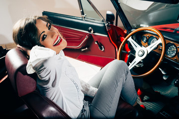 Smiling vintage woman in old red car
