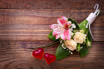 Wedding bridal bouquet of roses and lilies on wooden table