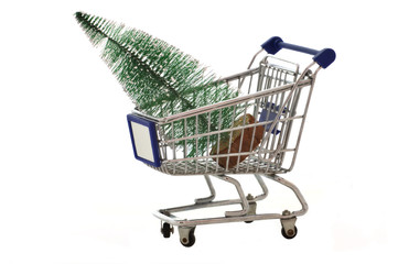 Grocery cart with Christmas tree isolated on white