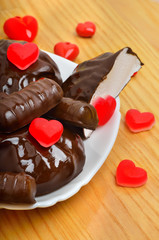 Сhocolate candies and a valentine heart on white plate on woode