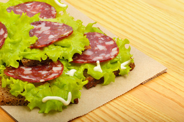 Bread with ham and lettuce on paper, on wooden background