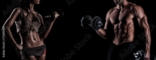 strong young couple working out with dumbbells. Shot in studio o - 75003885