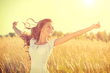 Beauty happy girl with blowing hair enjoying nature on the field