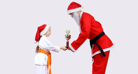 Santa Claus is giving little girl in karategi Cup of Karate