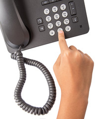 Female hand dialing numbers of desktop telephone