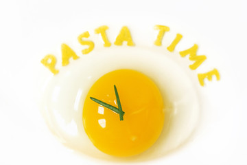 Raw egg in form of a clock with noodle letters for pasta time