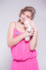 girl in a pink dress holding a teddy bear