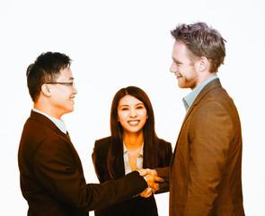Asian and caucasian men handshake agreement with smiling secreta