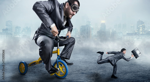 Nerdy businessman riding a small bicycle - 75010066