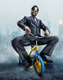 Fototapety Nerdy businessman riding a small bicycle