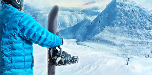 Rider with snowboard standing in the mountains