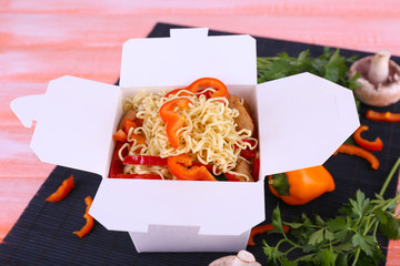 Chinese noodles in takeaway box on black mat on pink background
