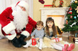 Santa Claus with two little cute girls near  fireplace and