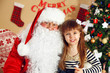 Santa Claus with little cute girl near  fireplace and Christmas