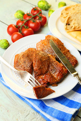 Roasted meat and vegetables on plate, on wooden table
