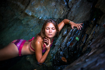 Beautiful sexy model posing in water of waterfalls wearing