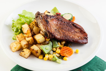 Fried pork with potatoes and vegetables salad