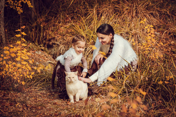 Mother and her daughter in vintage clothes with a cat