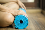Photo: Young woman holding a yoga mat