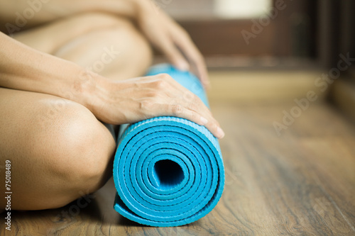 Young woman holding a yoga mat Plakát