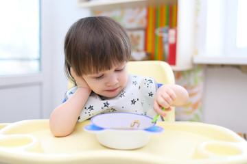 lovely little boy eating soup