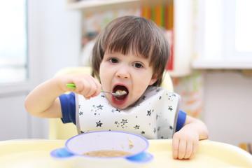 little boy eating soup