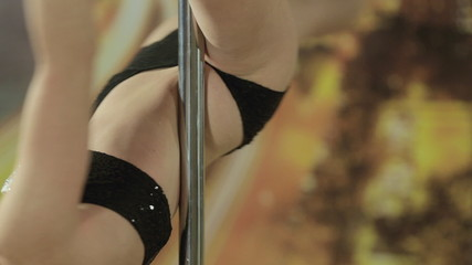 Close up of girl performing stunts on pole