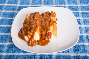 Two Chilli Dogs on White Plate and Blue Towel