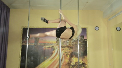 Attractive girl skillfully perform tricks on pole
