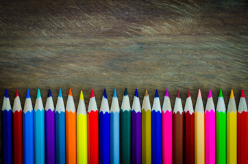 line of colored pencils on wood background