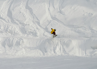 Jump of snowboarder at descent from mountain