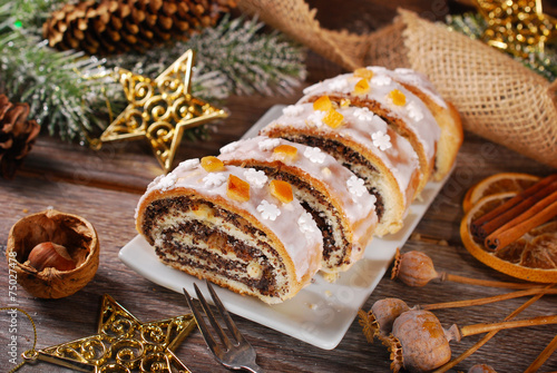 sliced christmas poppy seed cake with icing and snowflake sprink - 75027478
