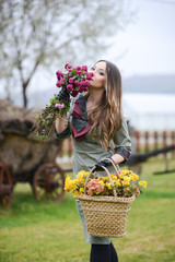 Woman of pretty woman collecting flowers in basket