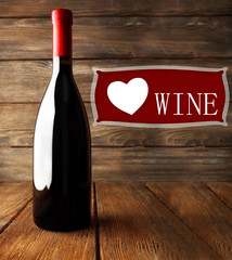 Bottle of red wine and space for text on wooden background