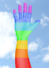 Man's hand painted as the rainbow flag on sky background