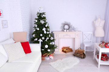 Beautiful Christmas interior with sofa, decorative fireplace