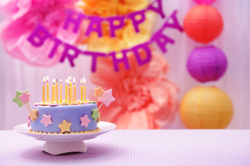 Delicious birthday cake on table on bright background