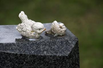 Zwei Vogelfiguren auf einem Grabstein