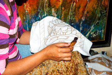 Woman applying wax on batik