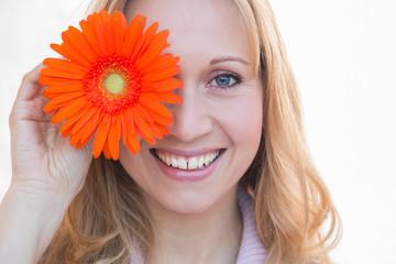 beautiful woman holding orange marguerite, selective focus