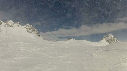 Skier carving and spraying snow at camera, real time