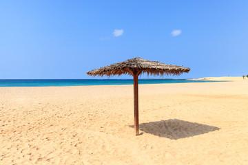 Beach scenery with parasol in Boavista, Cape Verde