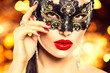 Sexy woman wearing carnival mask over holiday glowing background